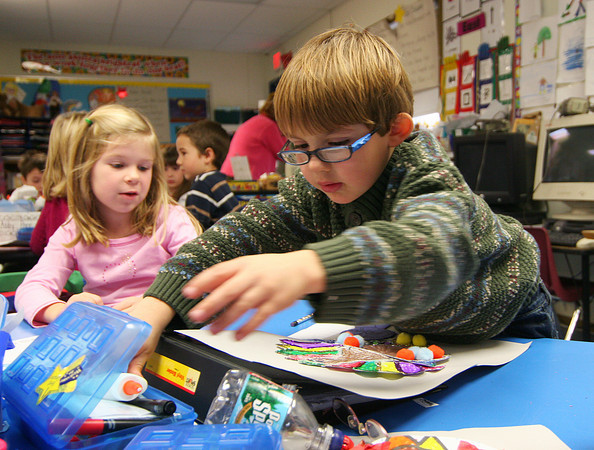Newburyport: Cruz Casella reaches for some art supplies while working on his Thanksgiving family turkey project in Susan LaBay's class at the Bresnehan Elmentary School in Newburyport Monday morning. Photo by Ben Laing/Staff Photo