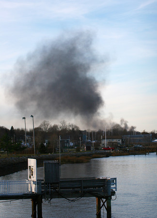 Newburyport: Smoke rises from a boat fire along Merrimac Street in Newburyport Monday afternoon, when a boat at the Newburyport Boat Basin caught fire. Photo by Ben Laing/Staff Photo