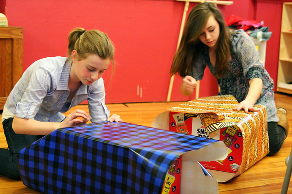 Newburyport: Sarah Simon 12, left, and Isa McGinnis, 13, right, wrap boxes at the drop in center at the Kelley School in Newburyport Monday afternoon, as they begin to decorate the school for Christmas. Photo by Ben Laing/Staff Photo