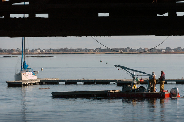 Newburyport: A work crew moves docks from the waterfront at Michael's Harborside in Newburyport to shore for storage, leaving only the dock that the pictured sailboat is tied to left in the harbor Monday morning. Bryan Eaton/Staff Photo