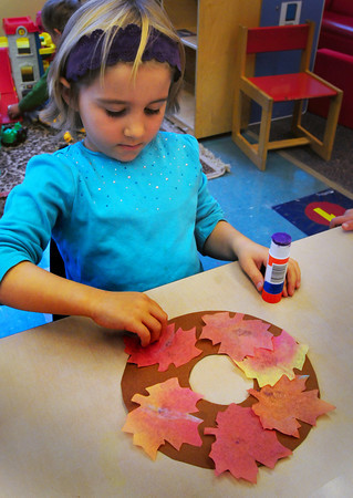 Newbury: Lia Hatheway, 4, glues fake leaves as she creates a wreath in Mary Jo Lagana's pre-kindergarten class at Newbury Elementary School on Thursday. The children were learning about deciduous trees. Bryan Eaton/Staff Photo