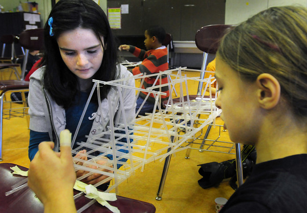 Amesbury: Fourth grade students at the Cashman School in Amesbury built bridges out of plastic straws, tape and pins to be judged for design, strength and function on Wednesday. Jillian Reid, 10, left, and Sara Johnson, 9, finish up their truss bridge model. Bryan Eaton/Staff Photo