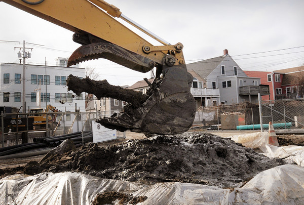Newburyport: A front-end loader drops one of several timbers believed to be part of Coombs Wharf at the site of the Water Treatment Plant which is getting renovated. Bryan Eaton/Staff Photo