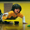 Newbury: Beck Hermann, 6, rolls along to grab one of several beanie bags in the middle of the Newbury Elementary School gym as they play Beanie-Baby-Pickup in Anna Molesso's class. At the end of the grab by four teams, each counted how many they had gotten. Bryan Eaton/Staff Photo