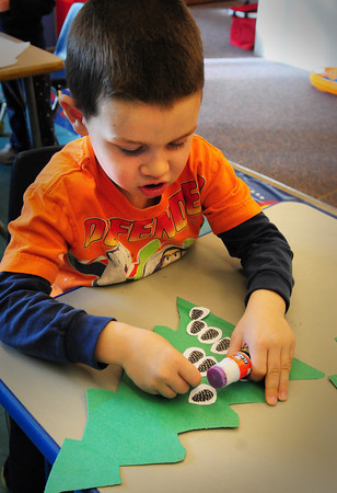 Newbury: Zachary Lyon, 4, glues pinecones onto a fir tree cutout in Mary Jo Lagana's pre-kindergarten class at Newbury Elementary School on Tuesday. The children had learned about deciduous trees earlier, and now were learning about conifers, which Christmas trees are. Bryan Eaton/Staff Photo