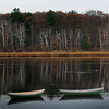 Amesbury: Dories frame a reflection of birch trees in the Merrimack River in a view from Lowell's Boat Shop on Monday morning. Bryan Eaton/Staff Photo