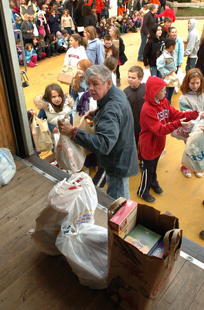 """Amesbury: Our Neighbor's Table volunteer Les Childs takes bags and boxes from Amesbury's Cashman School students they collected for the """"fill-a-cruiser"""" food drive Friday. They couldn't use police officer Thomas Hanshaw's cruiser, since they had over 2,000 items, so had to bring in the food pantry's truck. Bryan Eaton/Staff Photo"""