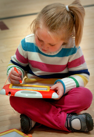 Newburyport: Matigan Richmond, 5, draws on a sketching device in the gym at the Brown School in Newburyport yesterday. She had just finished lunch and was with classmates for indoor recess due to the rain. Bryan Eaton/Staff Photo