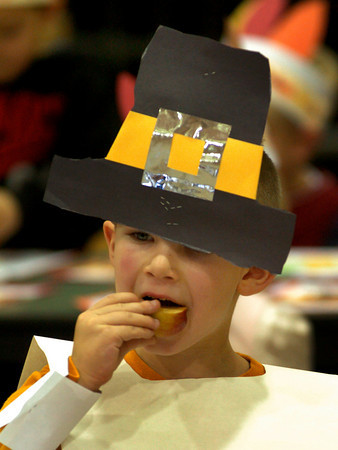 """Amesbury: Wearing his Pilgrim hat a little on the low side, Trey Marcotte, 5, eats some apple at a """"Friendship Feast"""" at the Cashman School on Tuesday. The kindergartners also had popcorn, and cornbread with butter students made themselves. Bryan Eaton/Staff Photo"""