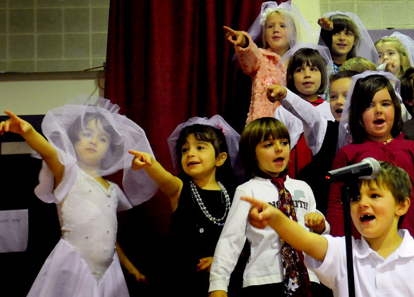 """Amesbury: Amesbury's Cashman School first-graders point to teacher Ashley Grimes as they sing Sonny and Cher's """"I Got You Babe"""" at a special assembly Friday morning for her wedding sendoff. Grimes and her fiance, Jay LaValley, made headlines last year when they won an all expenses paid wedding from Reason To Give, a group of small business owners from the North Shore who came together to present one deserving couple with a free wedding.Bryan Eaton/Staff Photo"""