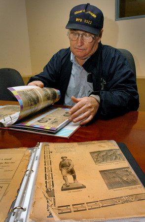 Newburyport: Mike Hartnett looks for familiar names in one of two scrapbooks he found recently while going through his late parent's home that contained clippings of those heading off to World War II and other related articles. Below is a scrapbook started with articles of the First World War, a picture of Amesbury's Doughboy shown. Bryan Eaton/Staff Photo