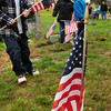 Amesbury: Cub Scouts from Amesbury Pack 4, including Jacob Darnell, 10, removed old flags from veteran's graves at Union Cemetery yesterday, replacing them with new ones. The worn flags will be properly retired by Amesbury Veteran's Agent Kristin LaRue along with World War II veteran Al LaValley. Bryan Eaton/Staff Photo