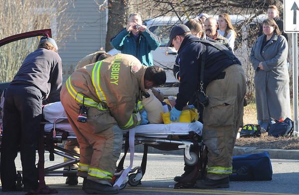 Salisbury: Firefighters and EMTs work on a victim at the scene of a 2 car crash on rt 110 ib Salisbury Sundaty morning. Jim Vaiknoras/Staff photo