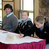 Byfield: The Governors Academy  hockey players Reed Kennedy, and Kate Leary look on as fellow hockey player Alex Carpenter her letter of intent to Boston College at a ceremony at the school Friday. Jim Vaiknoras/Staff photo