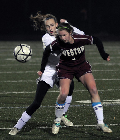 Lynn: Georgetown's Holly Sullivan fighs for the ball with Weston's Ilaria Santangelo during their game at Manning Field in Lynn Thursday night. Jim Vaiknoras/Staff photo