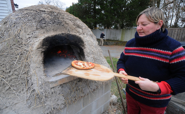 Newbury: Michelle Moon pulls a pizza from a newly constructed cob oven at the First Parish Church in Newbury Sunday afternoon. Jim Vaiknoras/Staff photo
