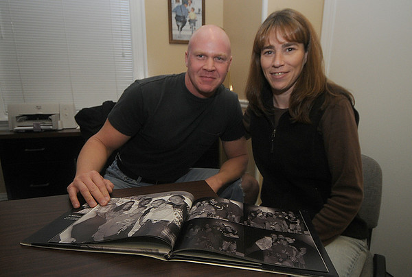 Amesbury: Justin Bybee's brother, Amesbury police Officer Larry Bybee, and close family friend, Jennifer Linscott, leaf through a book showing photos of Justin with members of his favorite band, Shinedown. Jim Vaiknoras/Staff photo