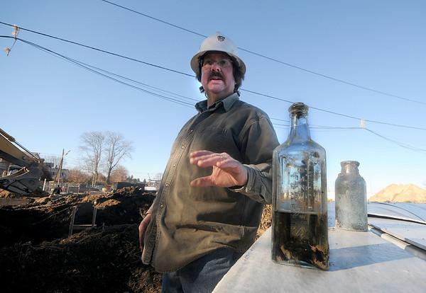 newburyport Archealogist Tim Barker talks about a Ayer's Sarsparilla bottle found at the water treatment plant constructiojn site in Newburyport. Jim Vaiknoras/Staff photo