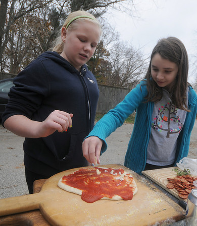 Newbury:Rebecca Pollock and Rose Coffey put topping on a pizza to be cooked in a newly constructed cob oven at the First Parish Church in Newbury Sunday afternoon. Jim Vaiknoras/Staff photo