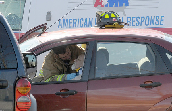 Salisbury: A firefighter works on a victim at the scene of a 2 car crash on rt 110 ib Salisbury Sundaty morning. Jim Vaiknoras/Staff photo