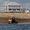 Newbury: A bulldozer pushes sand dredged from the Merrimack River along Plum Island a couple hundred yards north of the center in a view from offshore. Bryan Eaton/Staff Photo