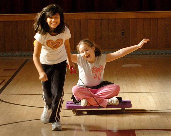 Newburyport: Angelica Soares, 9, pulls Katie Downey, 8, along on a rolling cart in new physical education teacher Jesse Craddock's class at the Bresnahan School yesterday morning. The students were doing different stations to work on muscle strength, the last week's classes working on aerobic excercises. Bryan Eaton/Staff Photo
