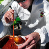 "Amesbury: Wearing a hazmat costume, Matt McLaughlin, a volunteer at the Amesbury Fire Department's chili booth, ladles out some ""hazmat"" chili Saturday. He was at the Sixth Annual Sizzlin' Hot Chili Cookoff sponsored by the department with proceeds going to the Shriner's Burn Institute Transport Fund. Bryan Eaton/Staff Photo"