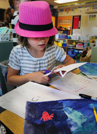 Amesbury: Emily York, 7, cuts out sea creatures, like the octopus below, for a mural in Lis Morris's class at Amesbury Elementary School yesterday as they're heading to the New England Aquarium next week. Emily was wearing a pink hat, coincidentally, as the school staff was wearing pink for Breast Cancer Awareness Month. Bryan Eaton/Staff Photo