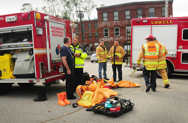 Amesbury: A state hazmat team gets their equipment ready to enter a building on Oakland Street in Amesbury, right, where there was a chemical spill in the basement. Bryan Eaton/Staff Photo