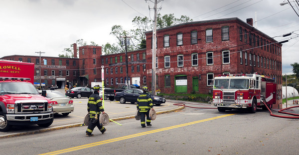 Amesbury: Firefighters bring extra hose in preperation before a state hazmat teams enters the building on the right on Oakland Street in Amesbury to access a chemical spill. Bryan Eaton/Staff Photo