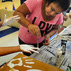 Salisbury: Savannah Hardin, 13, paints the hands of Boys and Girls Club counselor Courtni Welch white which she imprints onto some boxes in the Teen Center on Tuesday. Members of the Key Club there are making props for a haunted house at the end of October. Bryan Eaton/Staff Photo
