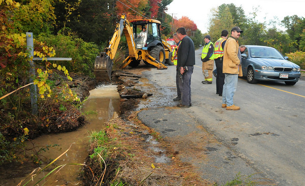 Newbury: Newbury public works department digs a trench along Middle Road to let water flow into a pump to send to the Little River. Beaver dams nearby have caused some flooding along the road. Bryan Eaton/Staff Photo