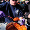 Amesbury: Newbury firefighter Rob Serino gives out a sample of his department's entry into the Sizzlin' Hot Chili Cookoff on Saturday in Amesbury. Theirs was a Jack Daniels Whiskey sauce with sausage, ground beef, red beans and othe secret ingredients. Bryan Eaton/Staff Photo