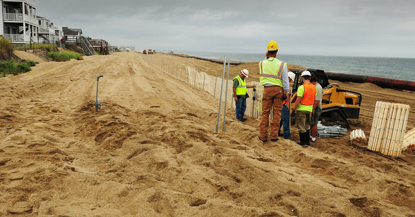 Salisbury: Crews were installing snow fencing along sections of Salisbury Beach after sand was deposited there from dredging of the Merrimack River. Bryan Eaton/Staff Photo