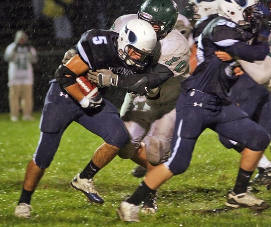 Byfield: Triton's Derek Paquette (5) drives through a Austin Prep tackler during Friday night's game in Byfield. Photo by Ben Laing/Staff Photo