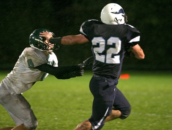 Byfield: Triton's Billy Murphy (22) stiff arms an Austin Prep defender on his way to the endzone during Friday night's game in Byfield. Photo by Ben Laing/Staff Photo