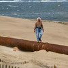 Newbury: A beach-goer walks atop the pipe running along Plum Island Monday afternoon, as the rough seas put the dredging project on hold. Photo by Ben Laing/Staff Photo