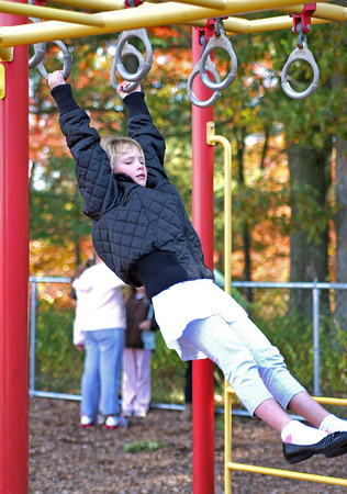 Rowley: Alice Thornton, a fourth grader at the Pine Grove School in Rowley, monkey's around on the rings during recess Monday afternoon. Photo by Ben Laing/Staff Photo