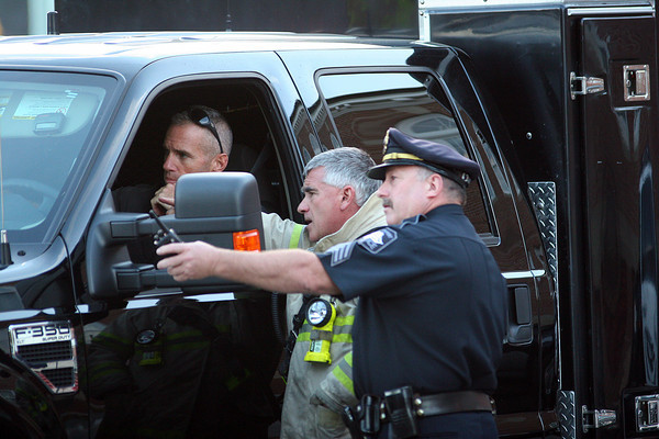 Newburyport: Newburyport Fire Chief Cutter and Sergeant Maguire of the Newburyport Police direct a State Police Bomb Squad technician to the location of a suspicious package found in the Green Street parking lot Monday afternoon. Photo by Ben Laing/Staff Photo