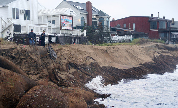 Newbury: Police and town officials investigate the damage to the sand bags at Plum Island center Wednesday morning after beach took another pounding from the recent storm. Photo by Ben Laing/Staff Photo