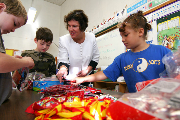 Newburyport: Bresnehan Elementary School principal, Kristina Davis, helps Andrew Cullen, left, John McCarthy, center, and Sami King, right, pack candy for the troops in Afgahnistan Monday morning. The second graders are in Mary Ellen Hoiseth's class, whose daughter, Jillian, is serving overseas. Photo by Ben Laing/Staff Photo