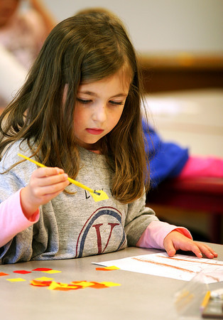 Newbury: Lily Westerman, a kindergartener at Newbury Elementary, works on putting leaves on her tree in Amy Merluzzi's art class Monday afternoon. Photo by Ben Laing/Staff Photo