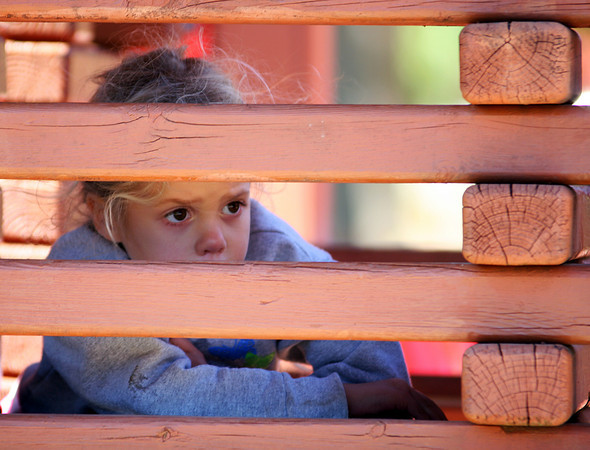 Amesbury: Grace Taylor, 5, of East Kingston, NH, peeks out from her hiding place at Amesbury Town Park during a Monday afternoon game of hide and seek. Photo by Ben Laing/Staff Photo