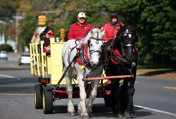Newbury: Draft horses from Colby Farm pull a group of hayriders down High Road in Newbury Wednesday morning. Photo by Ben Laing/Staff Photo