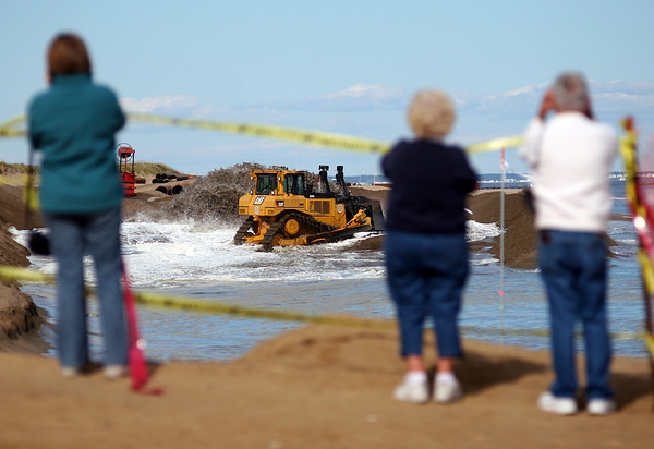 Newbury: Spectators flocked to the beach at Plum Island center to watch the dreged sand be distributed along the battered shore line. Photo by Ben Laing/Staff Photo