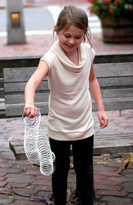 Newburyport: Elizabeth Denn, 7, of Chelmsford, plays with a Slinky Sunday afternoon in Market Square in downtown Newburyport. Photo by Ben Laing/Staff Photo