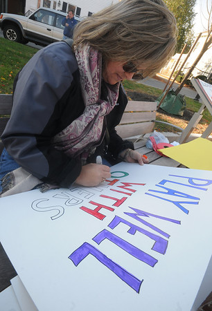 "Newburyport: Nancy Pollack of Richmond Me. color a sign the reads "" Play well with others"" at the Rally to Restore Sanity in Brown Square in Newburyport Saturday. Jim Vaiknoras/Staff photo"