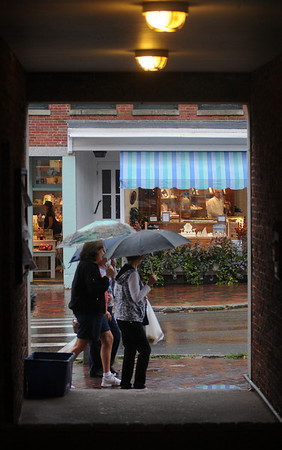Newburyport: A group of shoppers make their way  down State Street in the rain Friday afternoon. Jim Vaiknoras/Staff photo