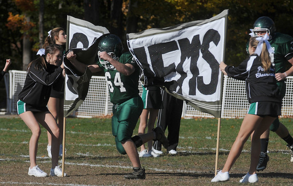 West Newbury: Pentucket high cheerlaeders hold tight to a Sachems sign as lineman Braeden Leach crashes through before their home game against Wilmington. The Sachems pulled out an 17-14 upset victory over the Wildcats. Jim Vaiknoras/Staff photo