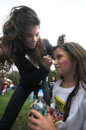 West Newbury: Ava Vecchi, 7, gets her face painted by Pentucket field hockey player Brooksie Robinson at the Apple Havest Road Race in West Newbury Sunday morning. Jim Vaiknoras/Staff photo